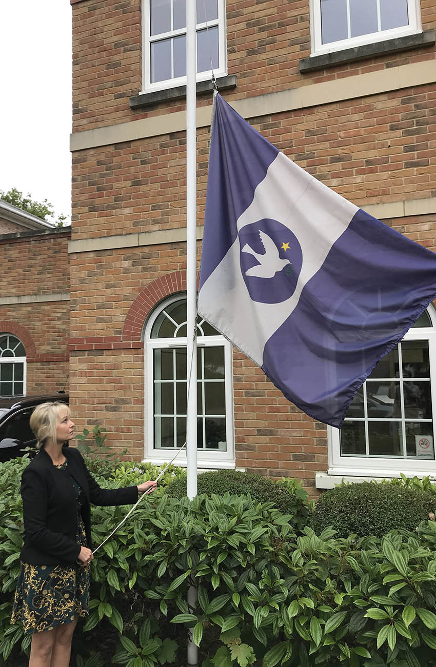 Sailors' Society's acting CEO Sandra Welch lowers the charity's flag in memory of those lost in the HMS Thetis tragedy